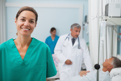 Smiling nurse in hopsital room with doctor talking to a patient in background